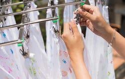 A mulher gravida seca o tecido de pano no sol Imagem de Stock