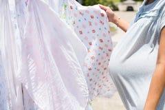 A mulher gravida seca o tecido de pano no sol Fotografia de Stock Royalty Free
