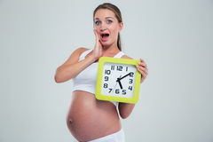 Mulher gravida surpreendida que guarda o pulso de disparo de parede Fotografia de Stock