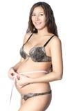 A mulher gravida tenta sobre sua barriga em um fundo branco. Imagens de Stock Royalty Free
