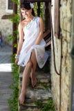 A mulher grega está sentando-se nas etapas de pedra Imagem de Stock