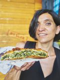 Mulher grega que come uma torta tradicional de Spanakotiropita, de espinafres e de feta Foto de Stock Royalty Free