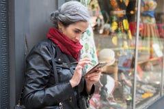 A mulher grisalho nova com bolsa e c?mera no pesco?o consulta seu telefone celular em Seattle imagem de stock