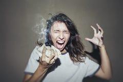A mulher grita e jura com um pedaço de papel amarrotado iluminado na Imagens de Stock