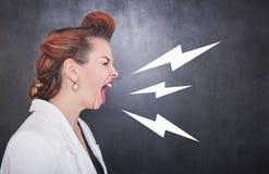 Mulher gritando irritada no fundo do quadro-negro fotos de stock