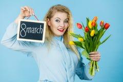 A mulher guarda as tulipas, placa com texto o 8 de março Fotografia de Stock Royalty Free