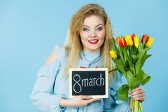 A mulher guarda as tulipas, placa com texto o 8 de março Fotos de Stock