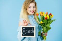 A mulher guarda as tulipas, placa com texto o 8 de março Fotos de Stock Royalty Free