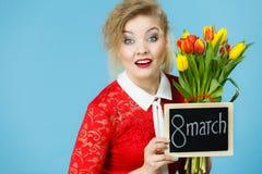 A mulher guarda as tulipas, placa com texto o 8 de março Imagens de Stock Royalty Free