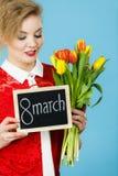 A mulher guarda as tulipas, placa com texto o 8 de março Foto de Stock Royalty Free