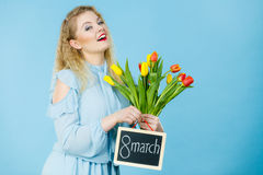 A mulher guarda as tulipas, placa com texto o 8 de março Imagem de Stock Royalty Free