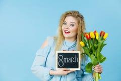 A mulher guarda as tulipas, placa com texto o 8 de março Fotografia de Stock