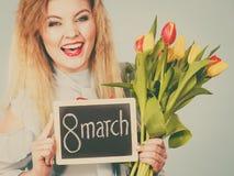 A mulher guarda as tulipas, placa com texto o 8 de março Foto de Stock