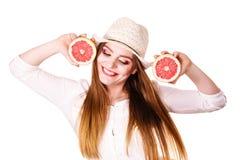 A mulher guarda dois halfs de citrinos da toranja nas mãos Fotografia de Stock Royalty Free