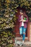 A mulher guarda livros e caminhada foto de stock