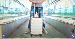 A mulher guarda a mala de viagem branca nas mãos e monta-a na escada rolante imagens de stock