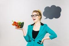 A mulher guarda o carrinho de compras com vegetais, espaço da cópia foto de stock