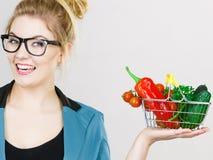 A mulher guarda o cesto de compras com vegetais imagem de stock