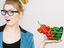 A mulher guarda o cesto de compras com vegetais fotografia de stock