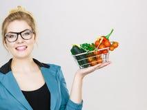 A mulher guarda o cesto de compras com vegetais foto de stock
