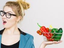 A mulher guarda o cesto de compras com vegetais foto de stock royalty free