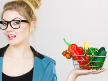 A mulher guarda o cesto de compras com vegetais imagens de stock