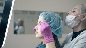 A mulher guarda a régua da testa na cara do cliente para verificar a tatuagem filme