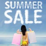 A mulher guarda sacos de compras sob o texto do verão Fotos de Stock Royalty Free