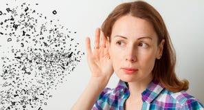 A mulher guarda sua mão perto da orelha e escuta imagem de stock royalty free