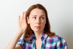 A mulher guarda sua mão perto da orelha e escuta imagens de stock royalty free