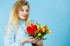 A mulher guarda tulipas e o coração vermelho Fotografia de Stock