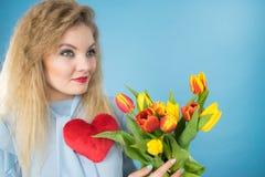 A mulher guarda tulipas e o coração vermelho Foto de Stock Royalty Free