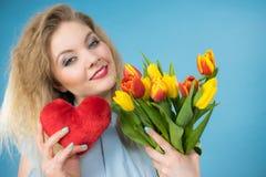 A mulher guarda tulipas e o coração vermelho Imagens de Stock Royalty Free
