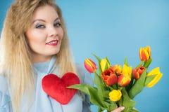 A mulher guarda tulipas e o coração vermelho Imagem de Stock