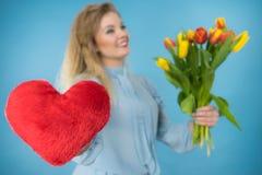 A mulher guarda tulipas e o coração vermelho Fotografia de Stock Royalty Free