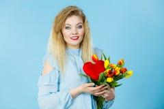 A mulher guarda tulipas e o coração vermelho Imagem de Stock Royalty Free