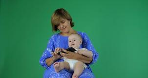 A mulher guarda um bebê que usa o telefone O bebê clica sobre o smartphone vídeos de arquivo
