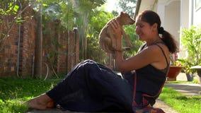 A mulher guarda um cachorrinho pequeno nas mãos O cachorrinho pequeno bonito lambe uma cara do ` s da mulher vietnam tiro do Lent vídeos de arquivo