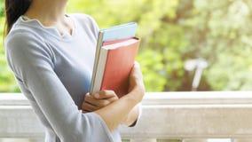 A mulher guarda um livro vermelho e um livro azul com o exterior Fotografia de Stock Royalty Free