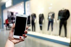 A mulher guarda um smartphone que está na frente de uma alameda Há um arquivo de Fotos de Stock Royalty Free