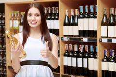 A mulher guarda uma garrafa de vinho na loja Fotografia de Stock Royalty Free