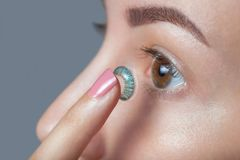 A mulher guarda uma lente de contato azul em seu dedo fotografia de stock royalty free