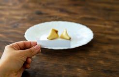 A mulher guarda uma nota vazia de uma cookie de fortuna em uma mão imagens de stock