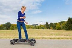A mulher holandesa conduz o mountainboard elétrico na natureza fotografia de stock royalty free