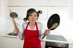Mulher home atrativa nova do cozinheiro no avental vermelho na cozinha que guarda a bandeja e o agregado familiar com o potenciôm fotos de stock