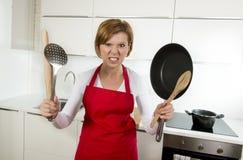 Mulher home do cozinheiro no avental vermelho na cozinha doméstica que guarda a bandeja e o agregado familiar no esforço foto de stock royalty free