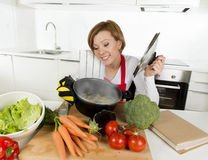 Mulher home do cozinheiro no avental vermelho na cozinha doméstica que guarda o cozimento do potenciômetro com o guisado vegetal  fotografia de stock royalty free