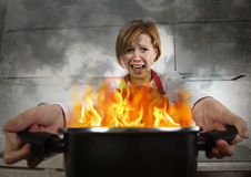 Mulher home inexperiente nova do cozinheiro no pânico com o avental que guarda o potenciômetro que queima-se nas chamas com em pâ Fotografia de Stock Royalty Free