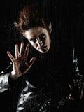 Mulher horrívea do vampiro atrás do indicador chuvoso Fotos de Stock Royalty Free