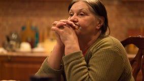 A mulher idosa é mãos tristes abraçadas junto e seus cotovelos na tabela vídeos de arquivo